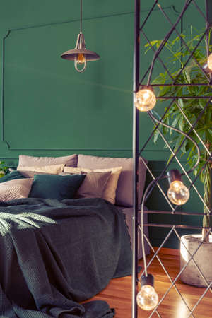 Beautiful bedroom interior with green design, copy space on empty wall