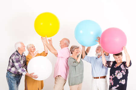 Happy elderly people playing with colorful balls in white room Фото со стока