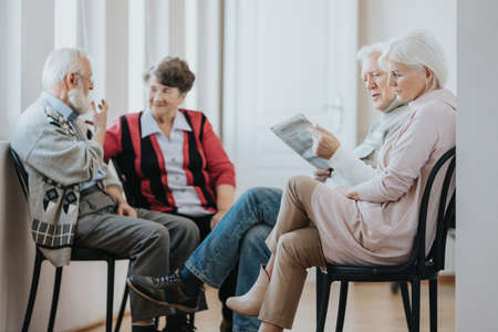 Group of older people sitting on chairs waiting in a line to the doctors office