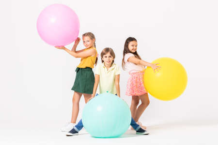 Two girls and a boy playing with balloons