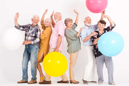 Happy old people hold colorful balls and they have their hands up