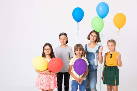 Smiling school kids with balloons prepared for a party