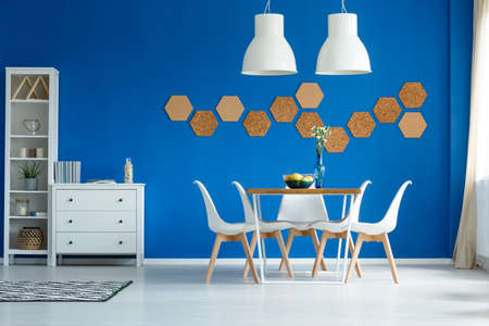 Cork honeycombs on blue wall of white living room with dining area