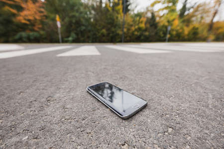 Close-up of lost new phone on the road