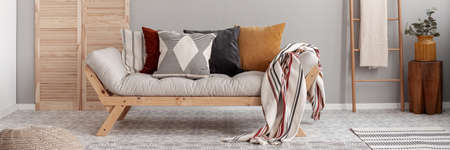 Dry flowers in white vase on small wooden table behind comfortable futon sofa with pillows Stockfoto