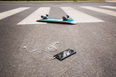 Upside-down skateboard and the phone on the street