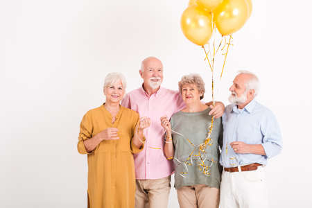 Happy seniors celebrating birthday in white room holding balloons Фото со стока