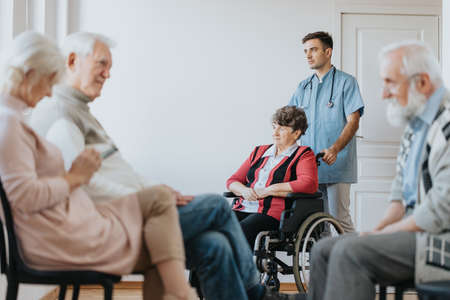 Young male nurse helping older woman on a wheelchair in a clinic Stok Fotoğraf
