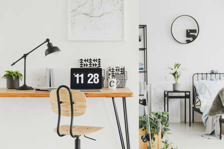 Map in white frame above green plant in black pot next to metal lamp and laptop on wooden desk in trendy kid's bedroom Zdjęcie Seryjne