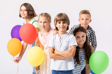 Group of smiling children with balloons on a white background Фото со стока