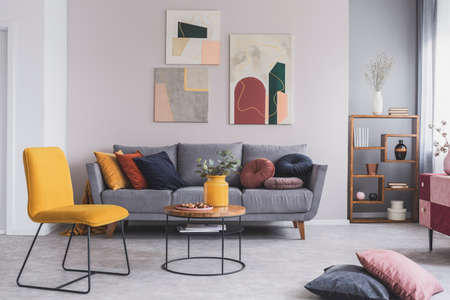 Real photo of a yellow chair and gray couch with pillows in a modern living room interior