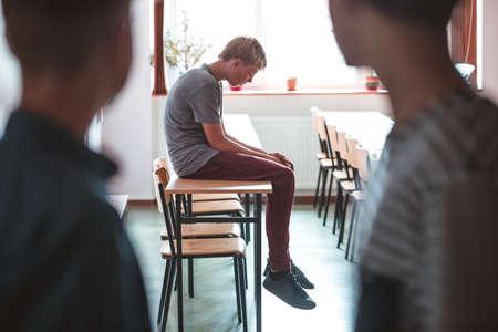 Sad teenage boy sitting alone at school, bullying among children concept
