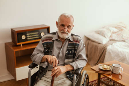 Senior man sitting lonely on a wheelchair at home Zdjęcie Seryjne