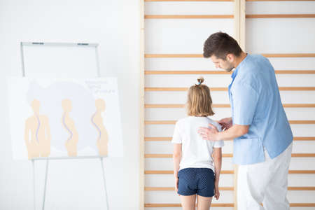 Male physiotherapist examining girl with scoliosis during rehabilitation Stock Photo