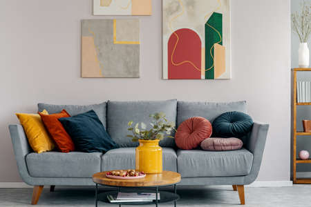 Colorful abstract painting above grey couch with pillows in scandinavian design interior