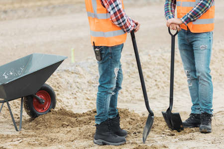 Two builders are leaning on shovels on the road construction site