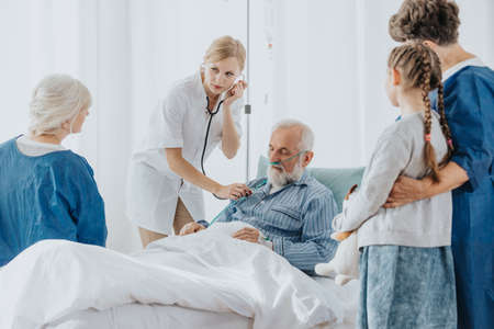 Sick senior man in hospital bed and young doctor checking his breathing