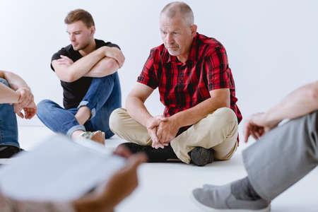 Groupe d'hommes exerçant leur imagination pendant la psychothérapie Banque d'images
