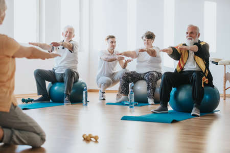 Group of senior people exercising on balls together in a gym