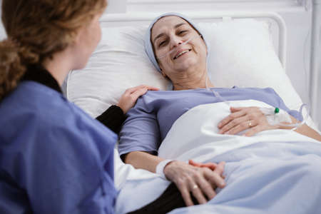 Helpful caregiver supporting sick woman with leukemia in the hospital