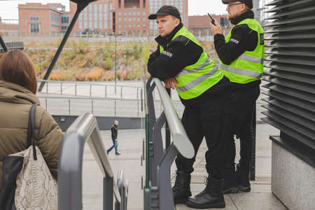Two young policemen in reflective jackets standing by the stairs and patrolling the street