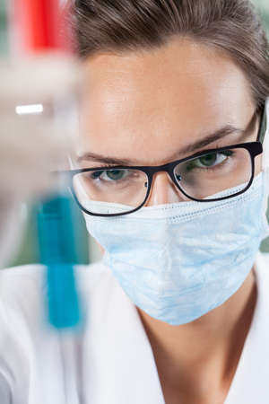 Female scientist in surgical mask examining test tube with blue liquid Фото со стока