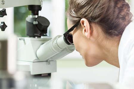 Woman working with microscope in a laboratory Фото со стока