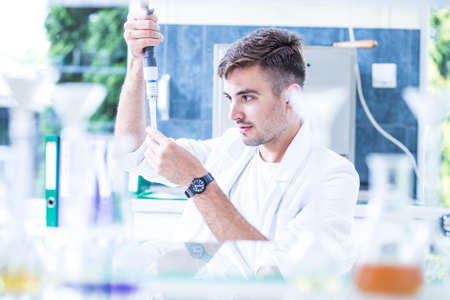 Young scientist during work on new vaccine in laboratory