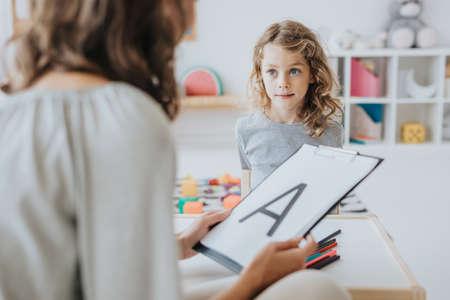 Teacher learning little girl the alphabet during classes