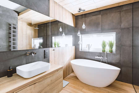Stylish bathroom with wooden and concrete walls and white bath