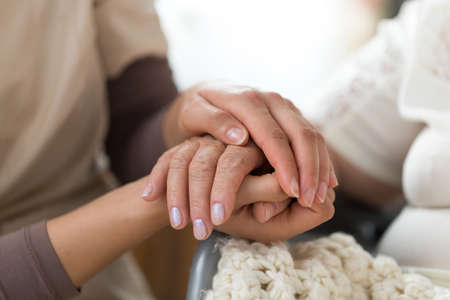 Closeup of hands of a young nurse holding hand of senior patient