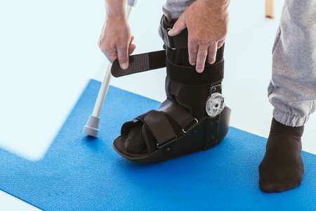 Patient in a black leg brace in a physiotherapy office