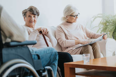 Two older disabled women sitting in a common room and waiting for the doctor
