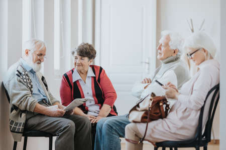 Group of older people sitting on a corridor waiting in a line to doctor's office Zdjęcie Seryjne