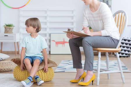 Autistic boy sitting next to psychotherapist during meeting in the school