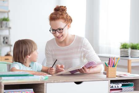 Happy mother and smiling son doing homework at desk Foto de archivo