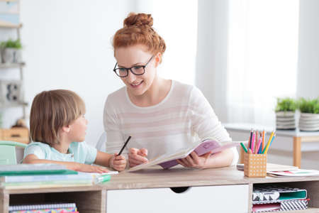 Happy mother and smiling son doing homework at desk Stock Photo