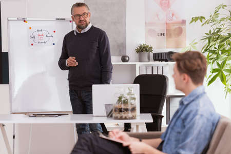 Middle aged therapist coaching young man during the session Stock Photo