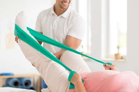 Physiotherpiast supporting woman exercising with elastic band