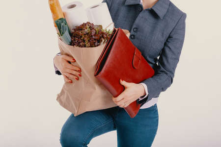 Woman in jeans and an elegant shirt is holding a leather briefcase and a paper shopping bag
