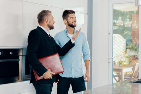 Businessman talking with smiling man about house for sale