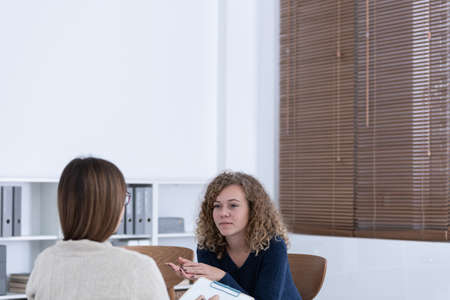 Professional counselor and woman suffering from depression during therapy Stock Photo