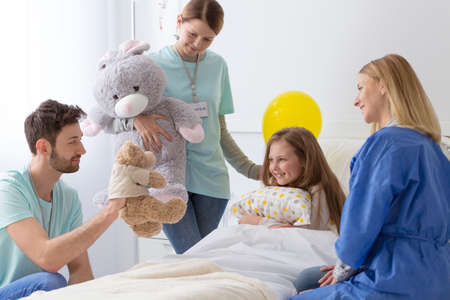 Loving family visiting little sick girl at the hospital Stock Photo