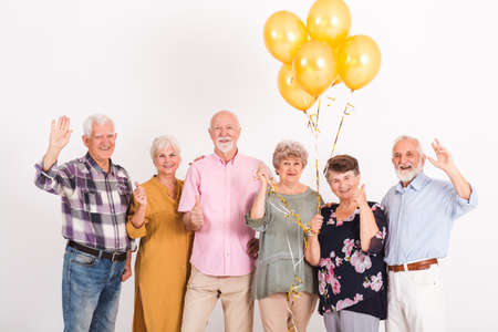 White interior with group of senior happy friends holding bunch of balloons