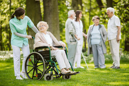 Group of senior patients with caregiver in the garden of nursing home Stock Photo