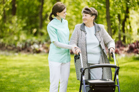 Senior disabled woman with caregiver in the garden of the nursing home