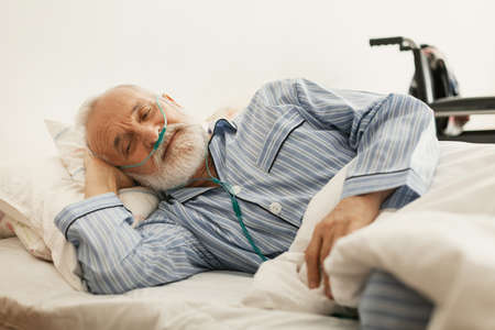 Older sick man with a oxygen mask lying in a hospital bed Stock Photo