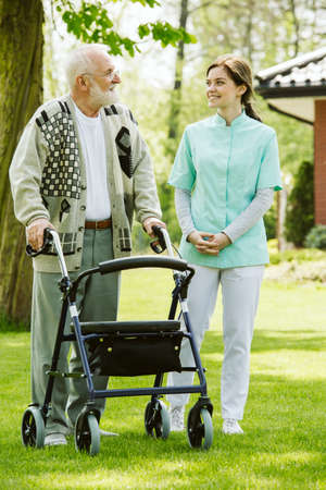 Senior man with walker during walk in the park of modern nursing home