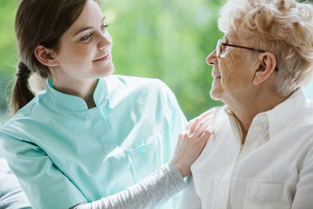 Happy senior woman and helpful caregiver, nursing home concept photos Stock Photo