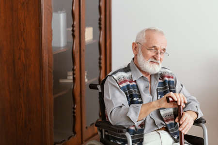 Older man with a walking stick sitting on a wheelchair home alone